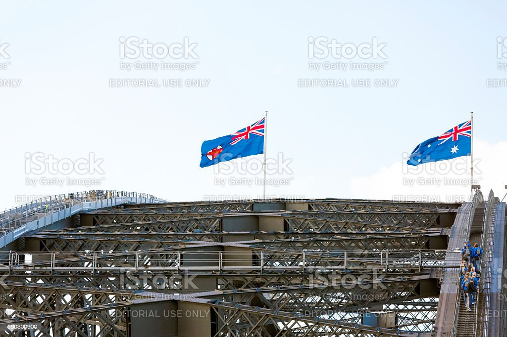 Harbour Bridge with Australian flags and climbing tourist, copy space stock photo