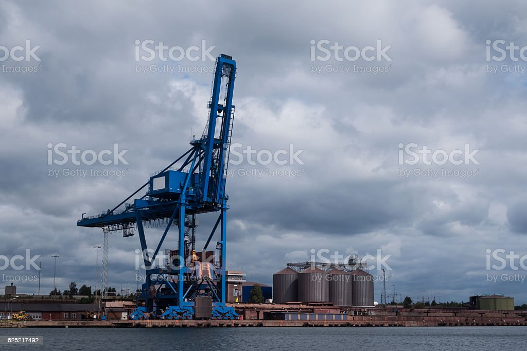 Harbour crane standing idle under cloudy sky stock photo