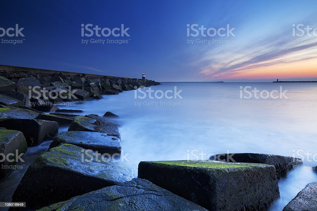 Harbour entrance at sea in IJmuiden, The Netherlands at dusk stock photo