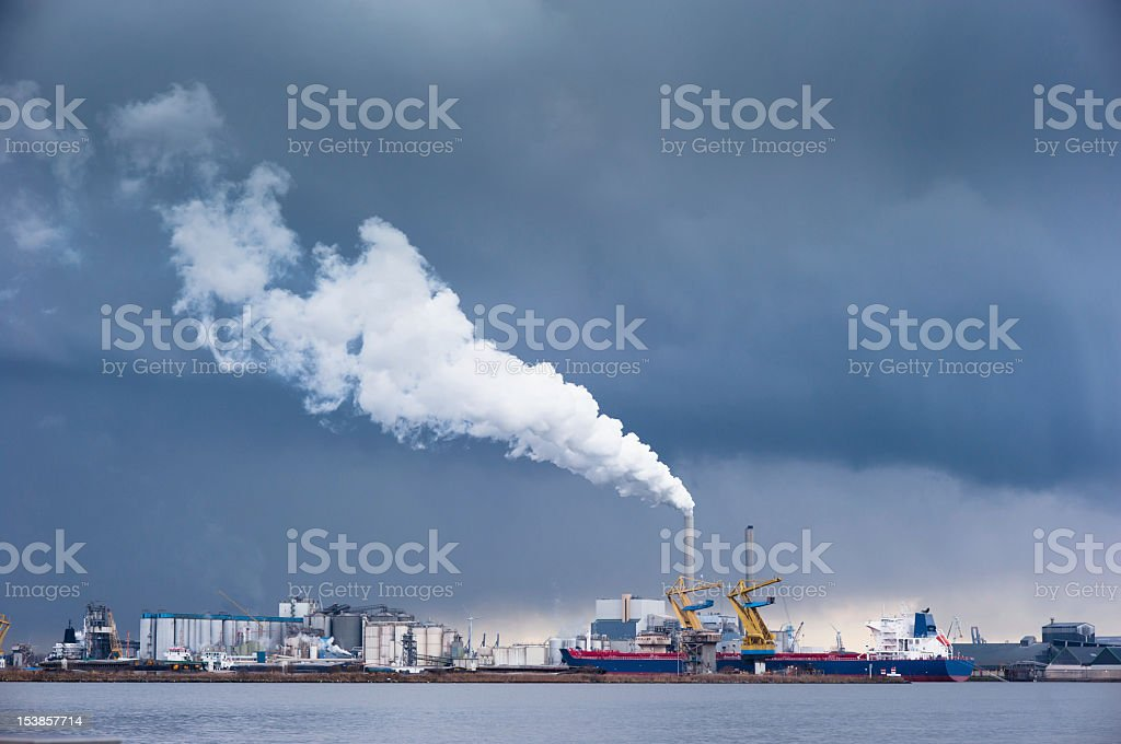 Harbour factory chimney blowing white smoke out - bad weather stock photo