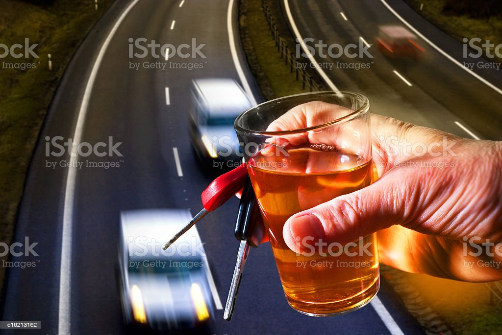 hard drinker with liqueur glass and going cars stock photo