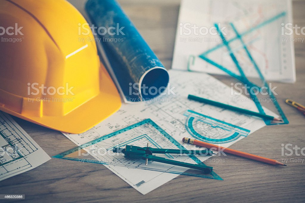 Hard hat and blue prints stock photo