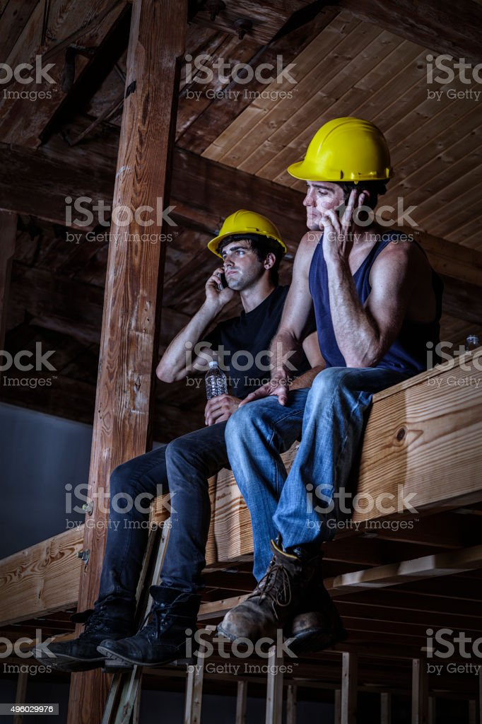Hard Hat Construction Workers Resting On Night Shift Work Break stock photo