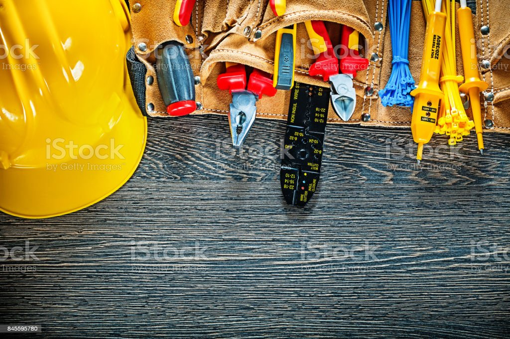 Hard hat leather tool belt on wooden board electricity concept stock photo