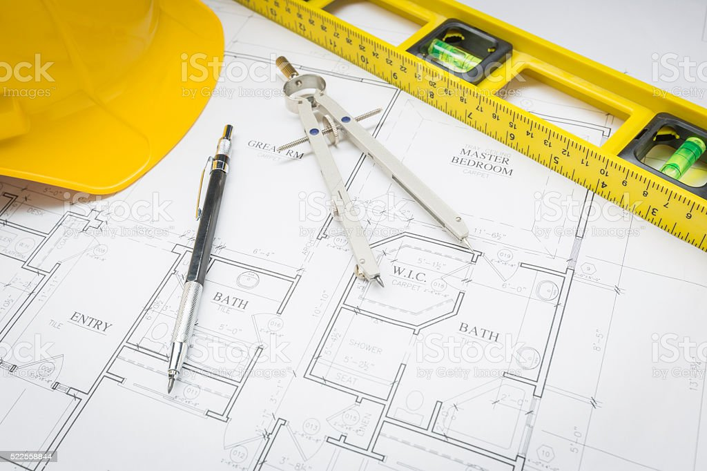 Hard Hat, Pencil, Level and Compass Resting on House Plans stock photo