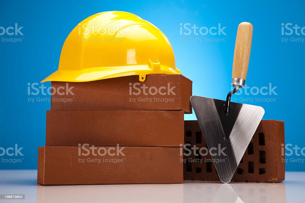 Hard hat with bricks and trowel royalty-free stock photo