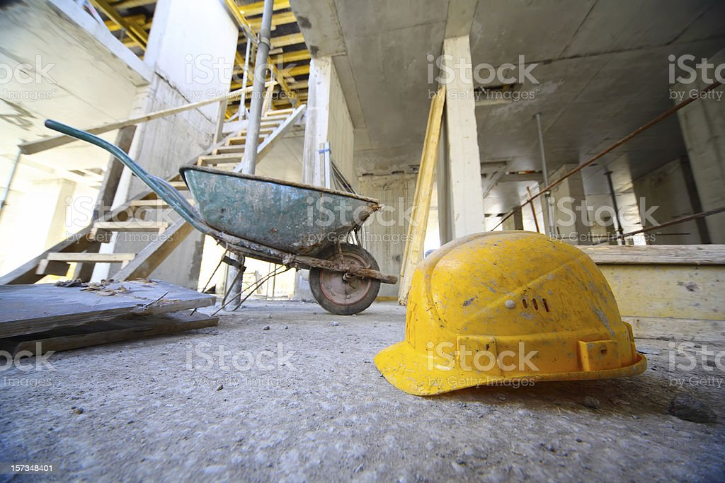 Hard hats and cart on concrete floor inside unfinished building royalty-free stock photo