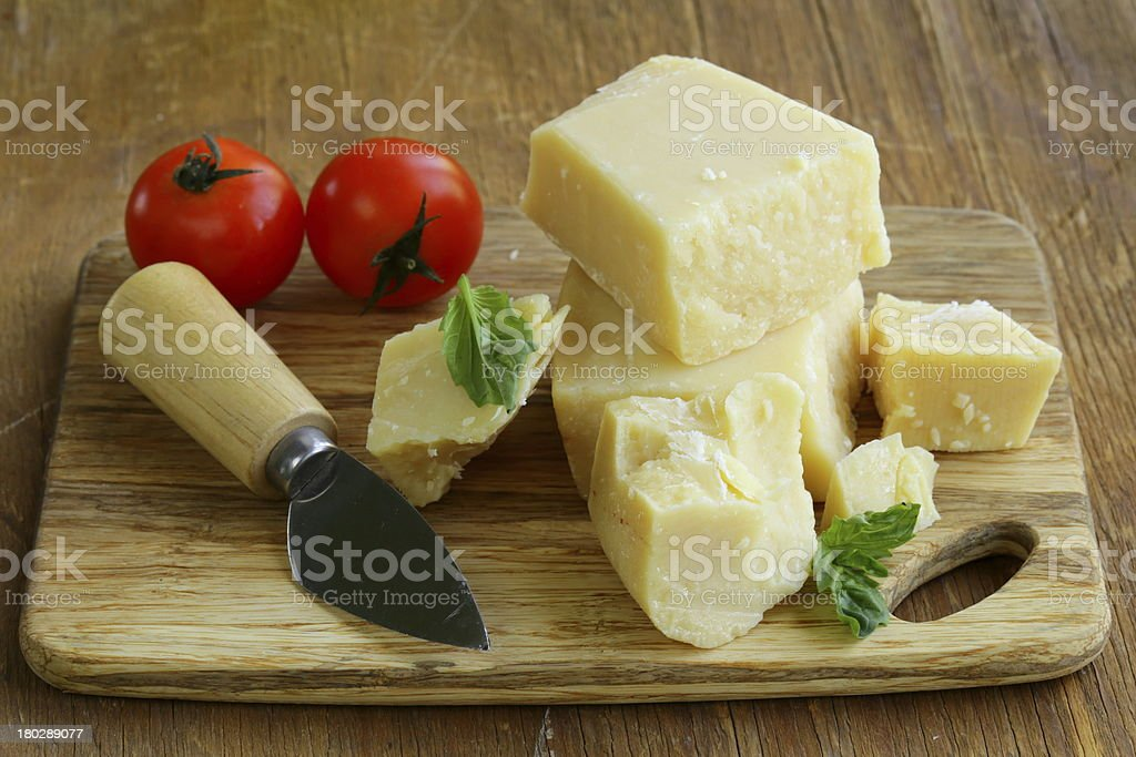 Hard natural parmesan cheese on a wooden board royalty-free stock photo