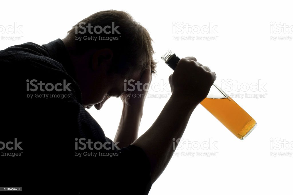 Hard times of a man holding an alcohol bottle stock photo
