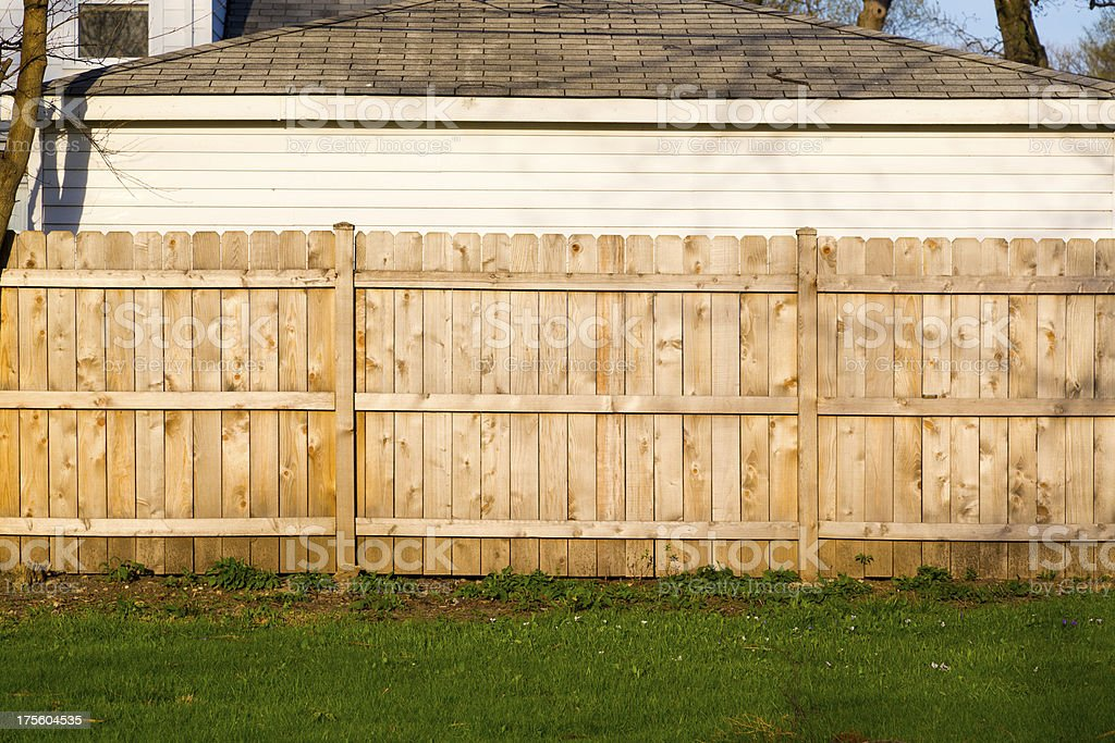 A hard wood fence outside a house stock photo