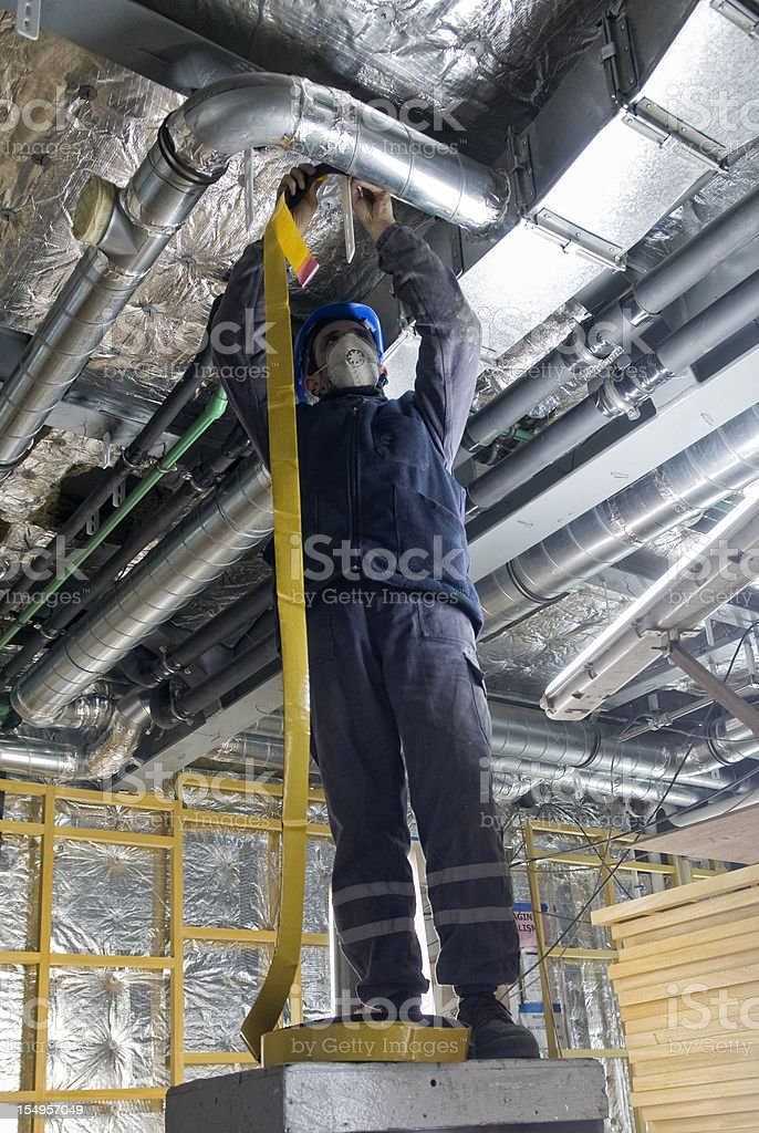 Hard worker wrapping an HVAC Air duct with foil tape royalty-free stock photo