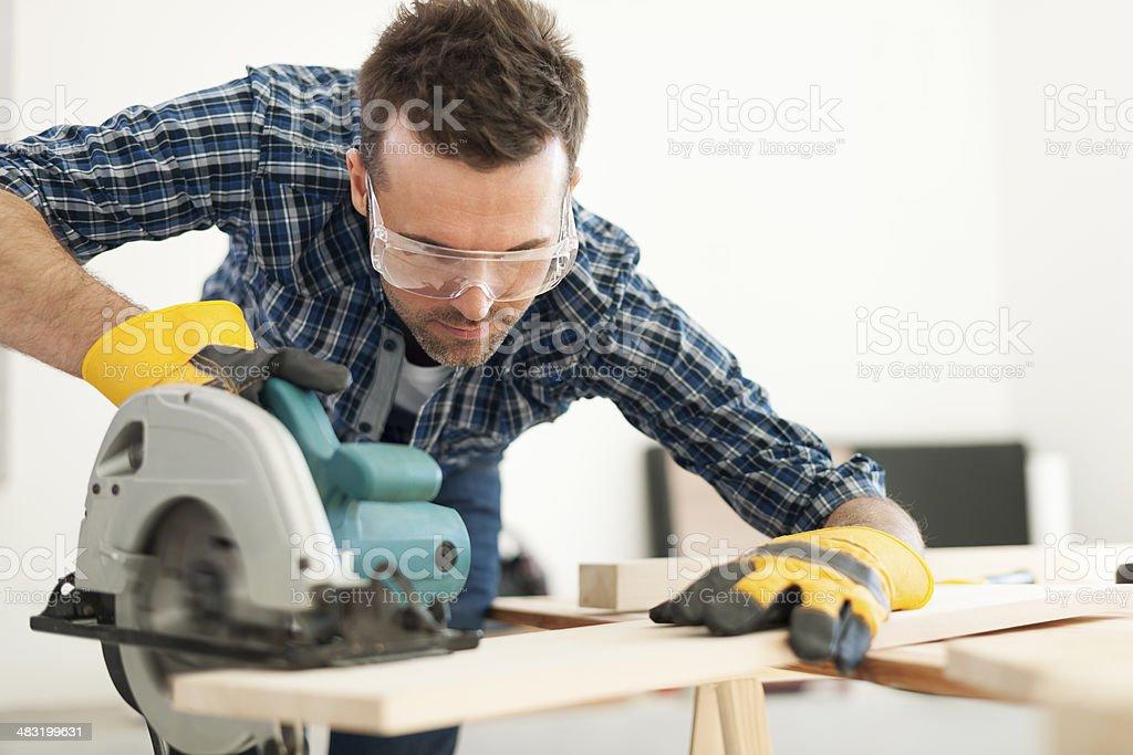 Hard working carpenter cutting wooden plank stock photo