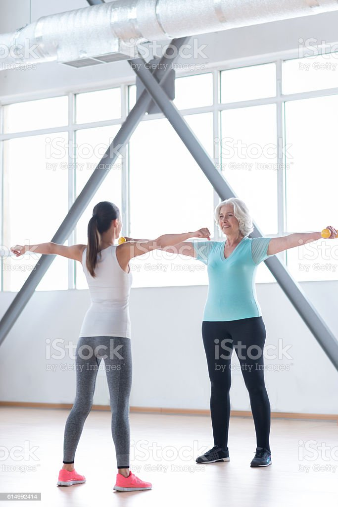 Hard working persistent woman repeating the exercise after the coach stock photo
