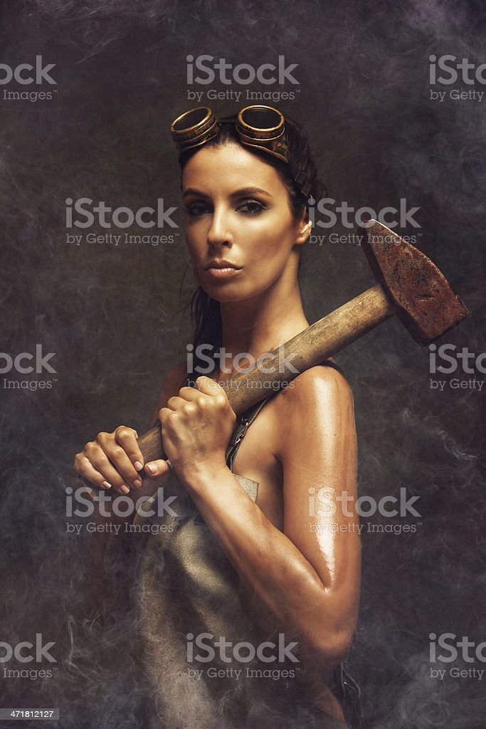 hard working woman holding a big hammer royalty-free stock photo
