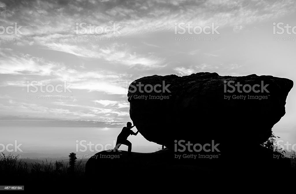Hard work.The person rolls the rock on mountain stock photo