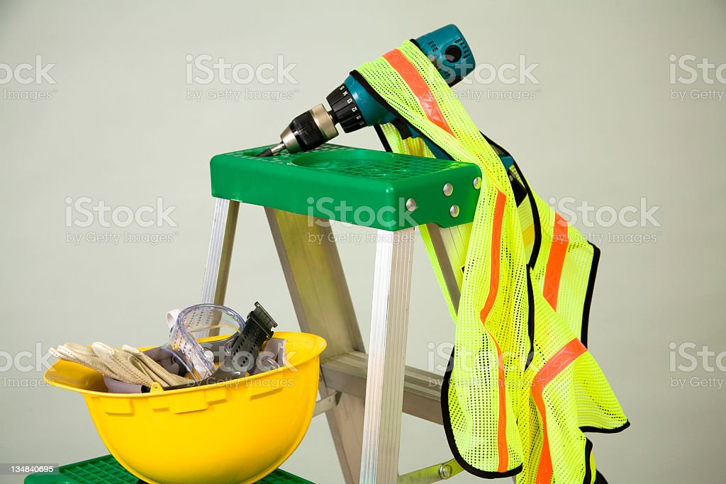 Hardhat, goggles, gloves, drill and safety vest on ladder. Construction. royalty-free stock photo