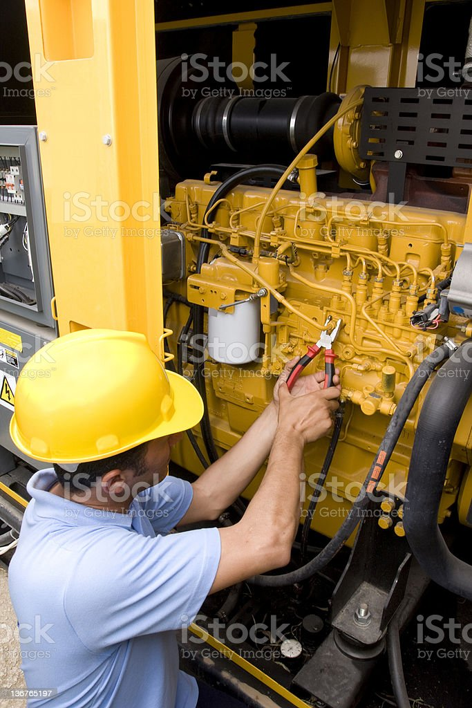 Hard-hatted mechanical technician working on machinery stock photo