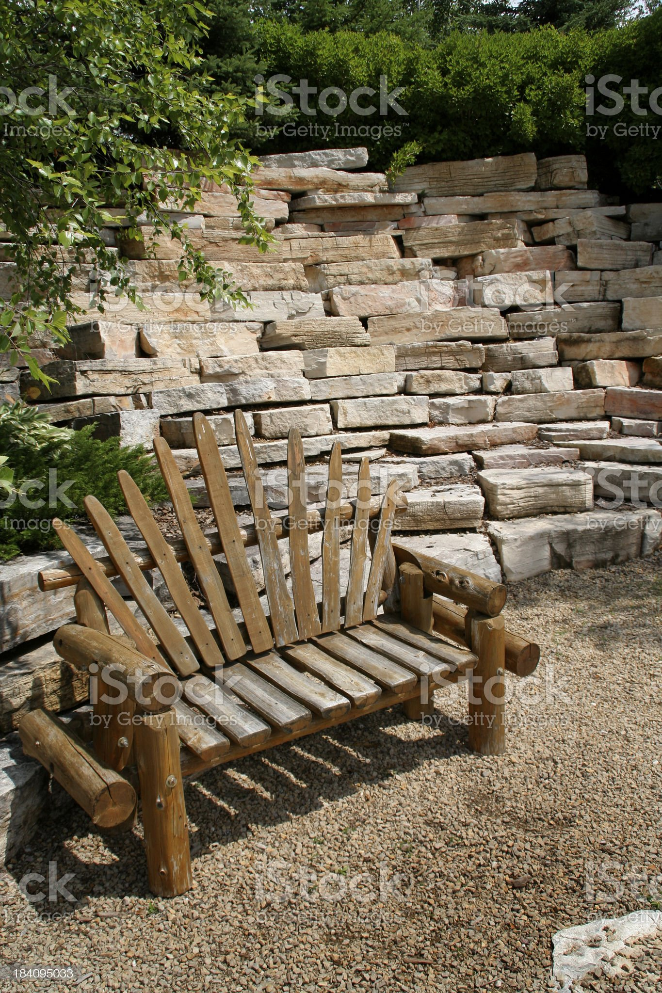 Hardscape Garden Landscaping with Rustic Log Bench, Rock, Stone Wall royalty-free stock photo