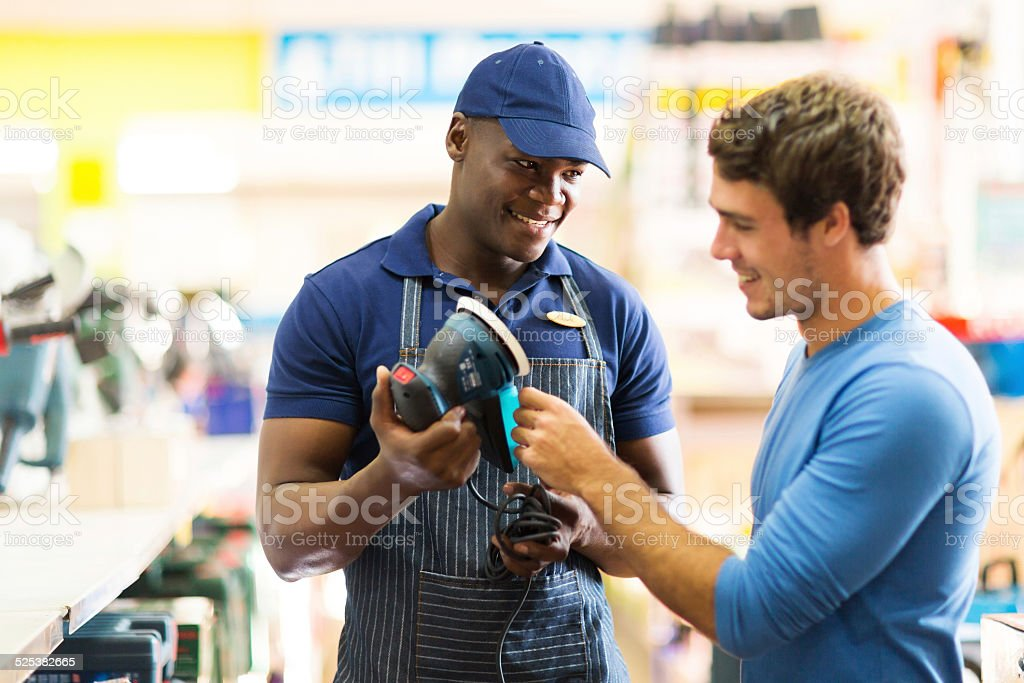 hardware store worker showing customer a sander stock photo