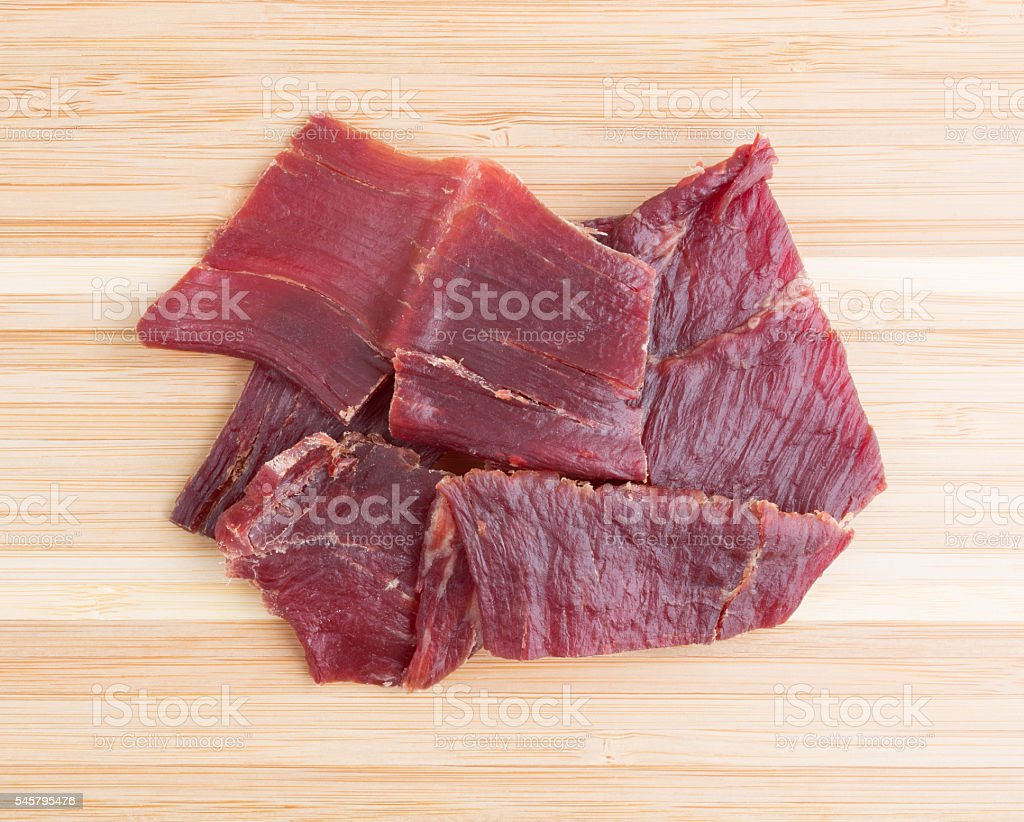 Hardwood smoked beef jerky on a cutting board stock photo