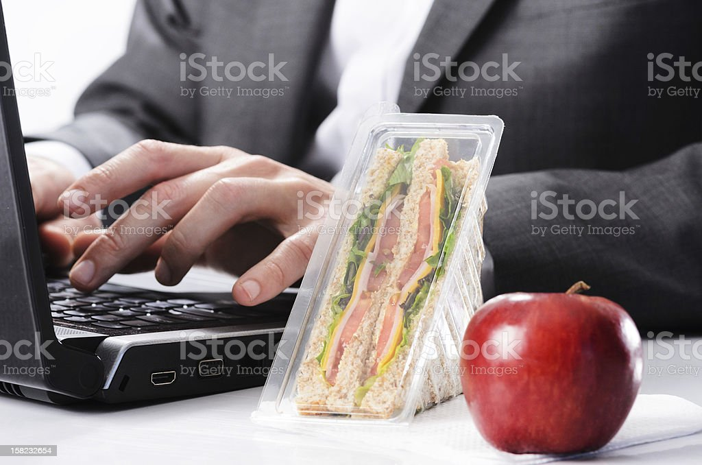 Hardworking businessman with uneaten lunch royalty-free stock photo