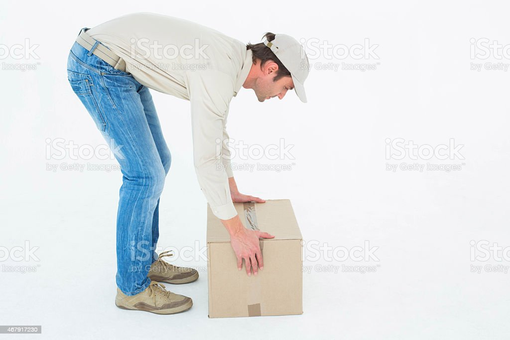A hardworking delivery man picking up a cardboard box stock photo
