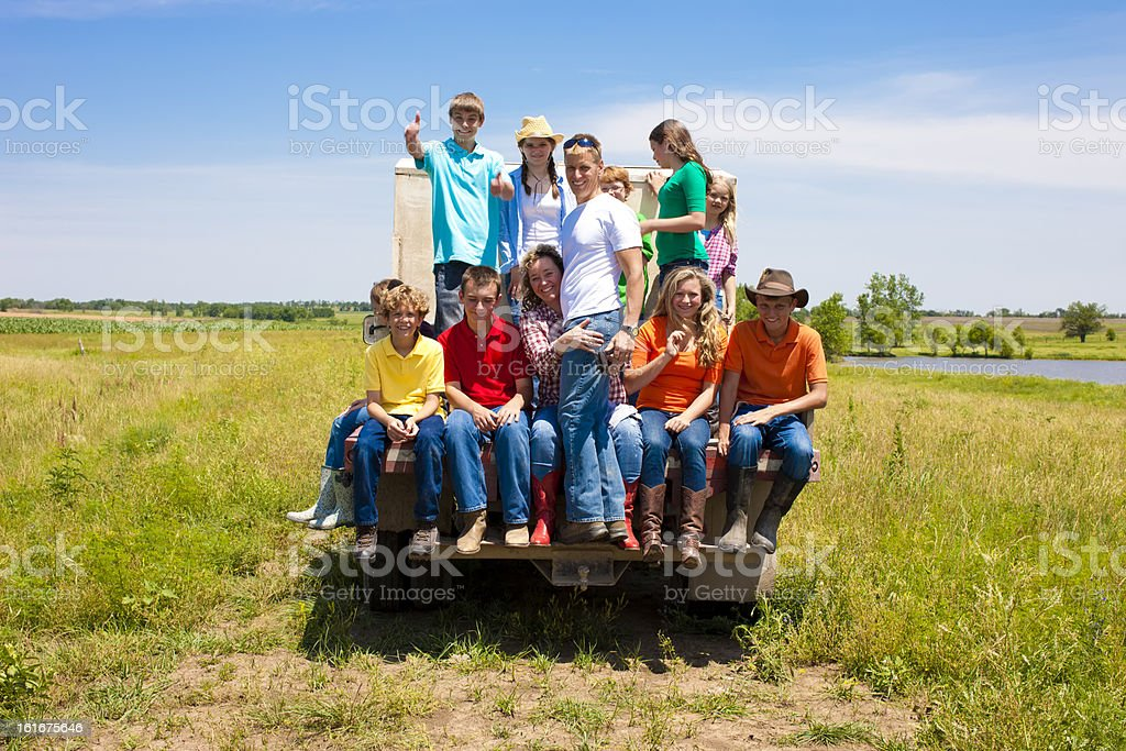 Hardworking Family Farmers Riding Bed of Truck on Farm stock photo