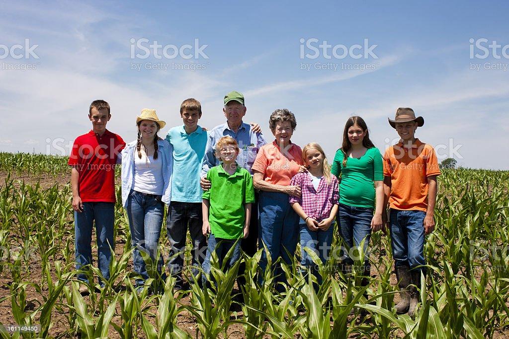 Hardworking Grandparents Farmers Standing with Grandchildren  in stock photo