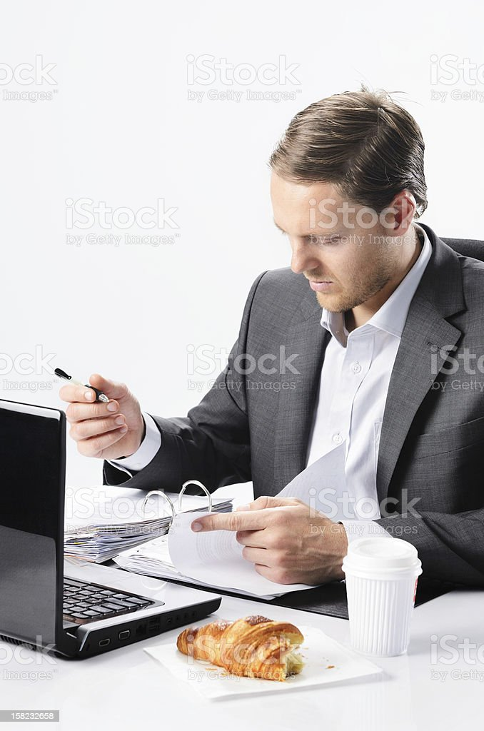 Hardworking man in suit with half eaten croissant royalty-free stock photo