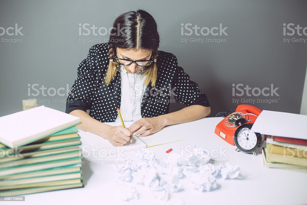 Hardworking nerd girl writing stock photo