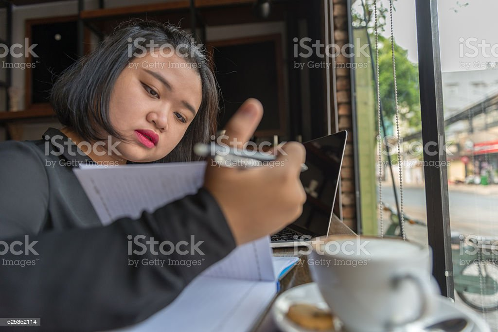 Hard-working student trying to finish her homework before deadline stock photo