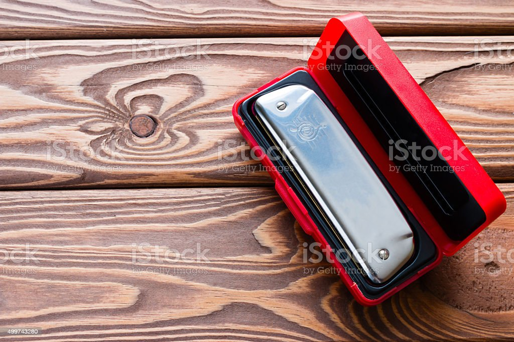 harmonica in a red box on a wooden background stock photo