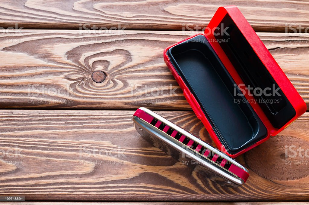 harmonica next to the packaging on the wooden background stock photo