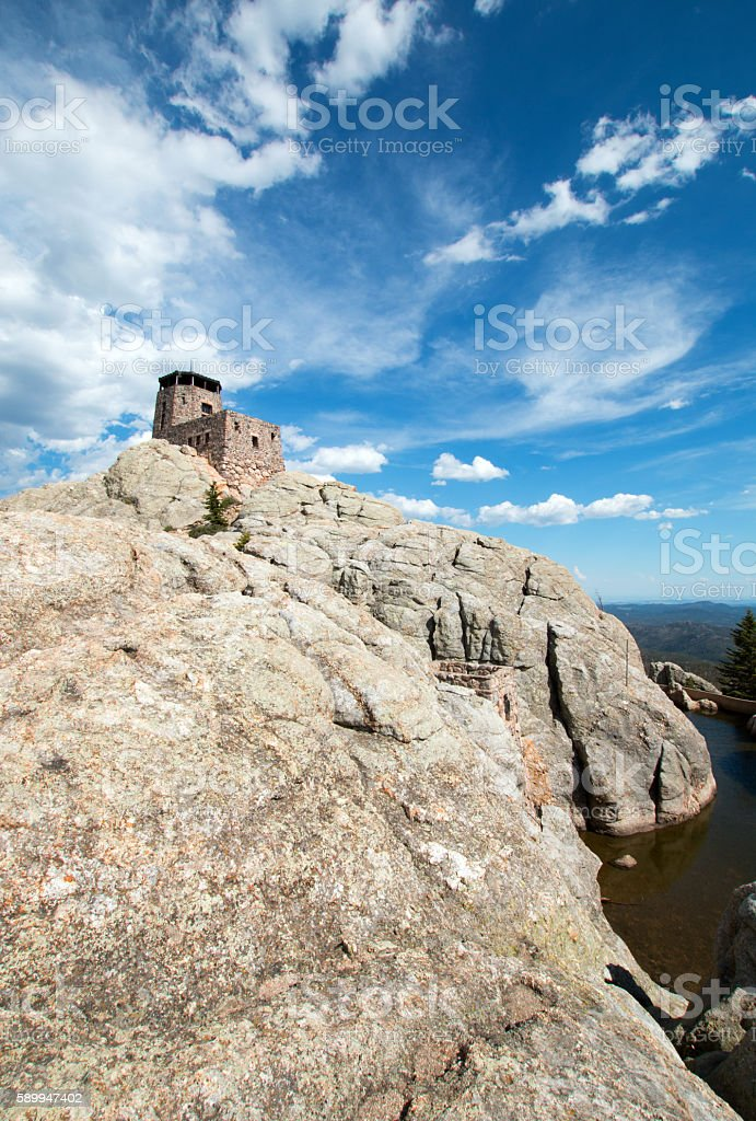 Harney Peak Fire Lookout Tower under expansive cloudscape stock photo