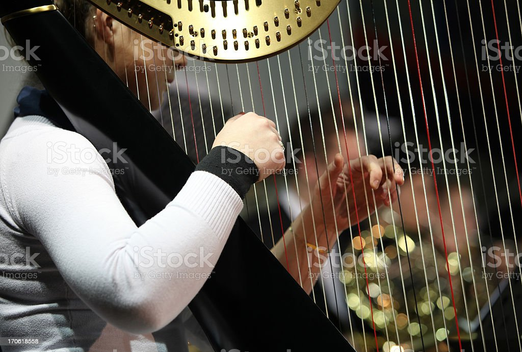 Harpist playing at concert...orchestra in the back stock photo