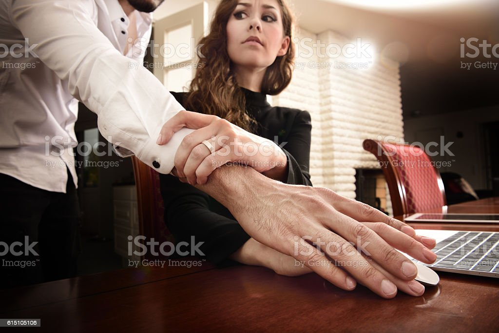 Harrassed woman removing his hand. She wears ring. stock photo