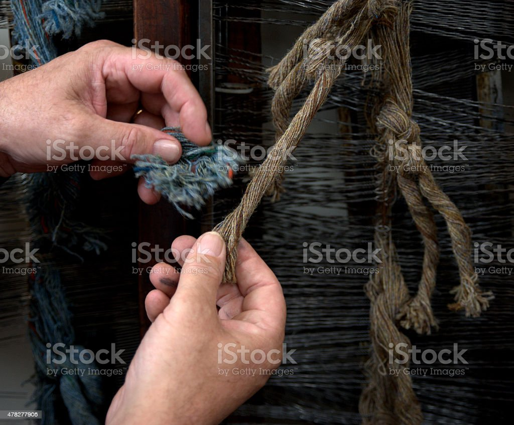 harris tweed threads on loom with weavers hands stock photo