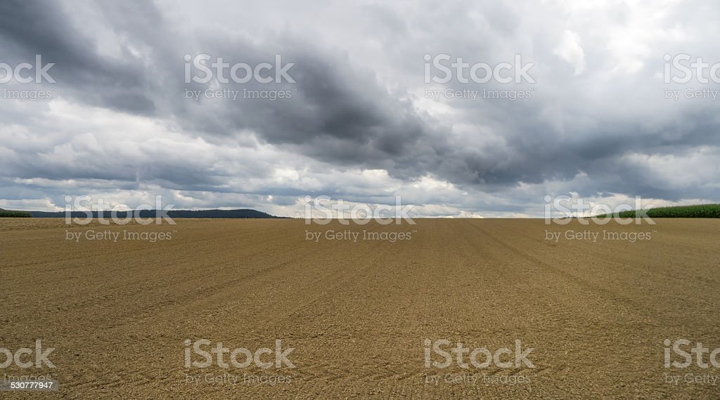 Harrowed field with dark clouds royalty-free stock photo