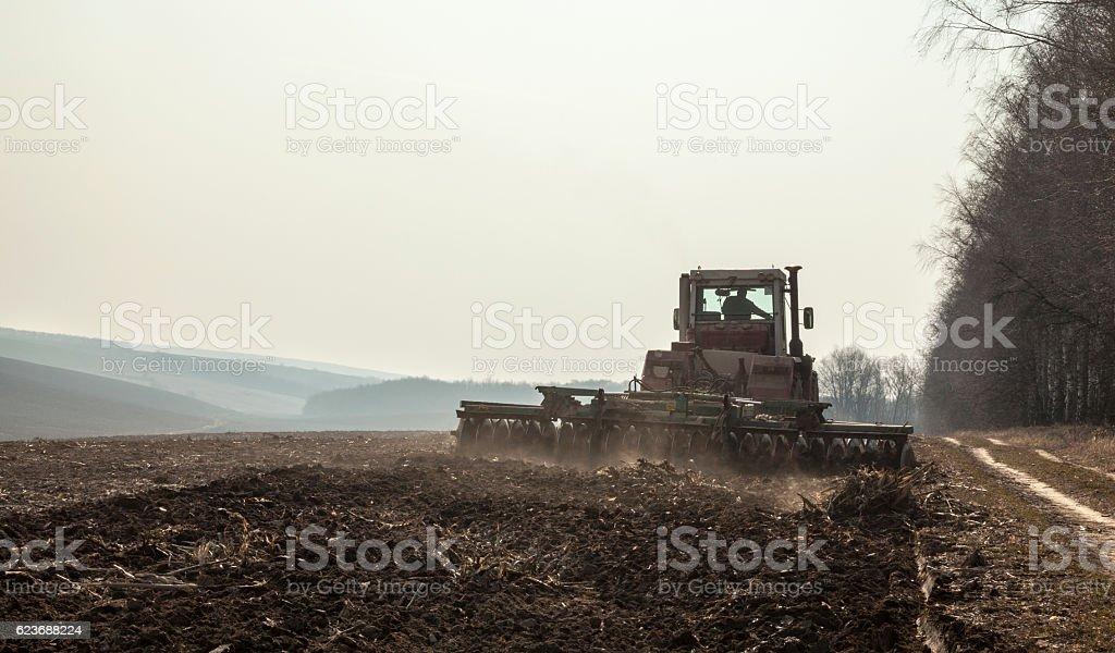 Harrowing the soil with disc harrows stock photo