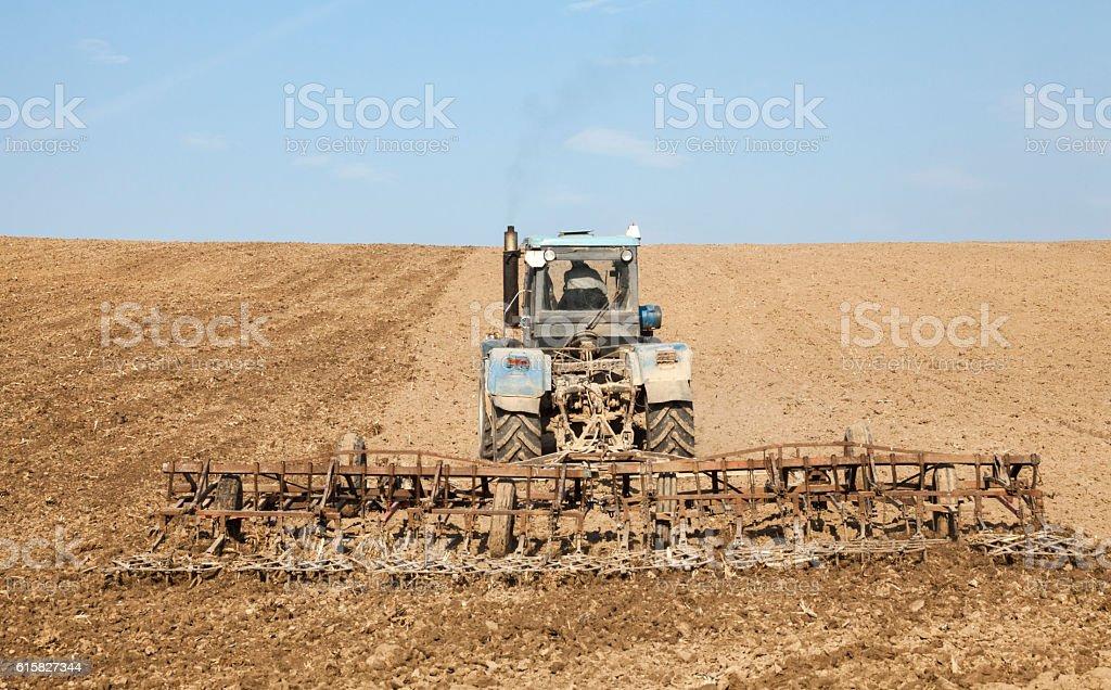 Harrowing the soil with tine harrows stock photo