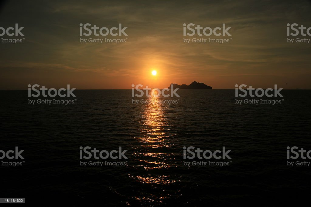 Harsh light of sunset in middle of ocean with island. stock photo