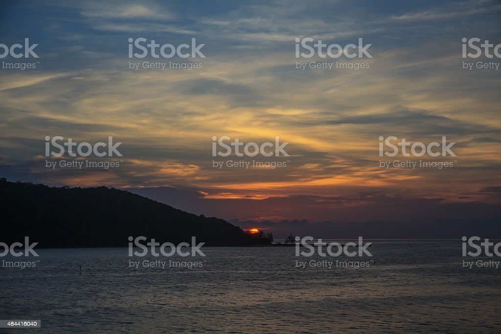 Harsh light of sunset in middle of ocean with island stock photo
