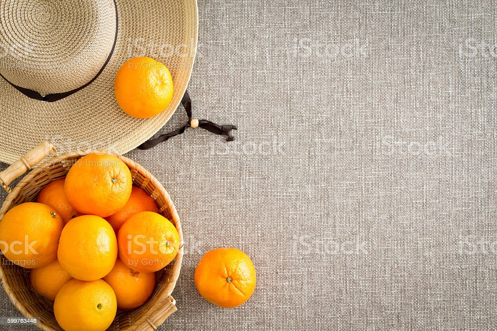 Harvest of farm fresh oranges with a straw sunhat stock photo