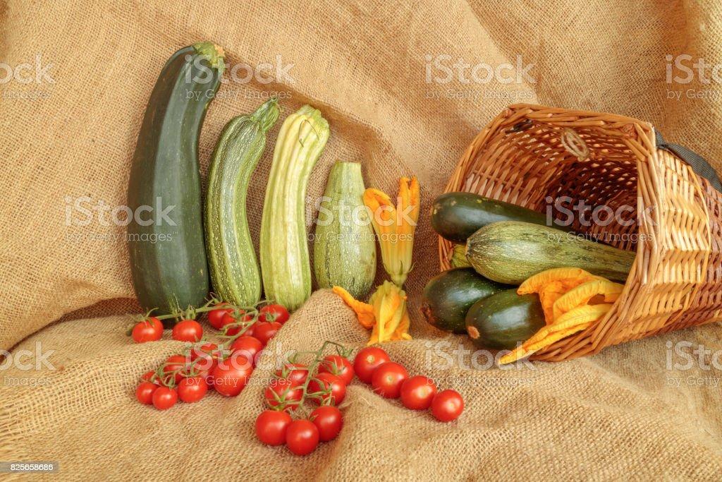 Harvest of zucchini and cherry tomatoes on jute stock photo