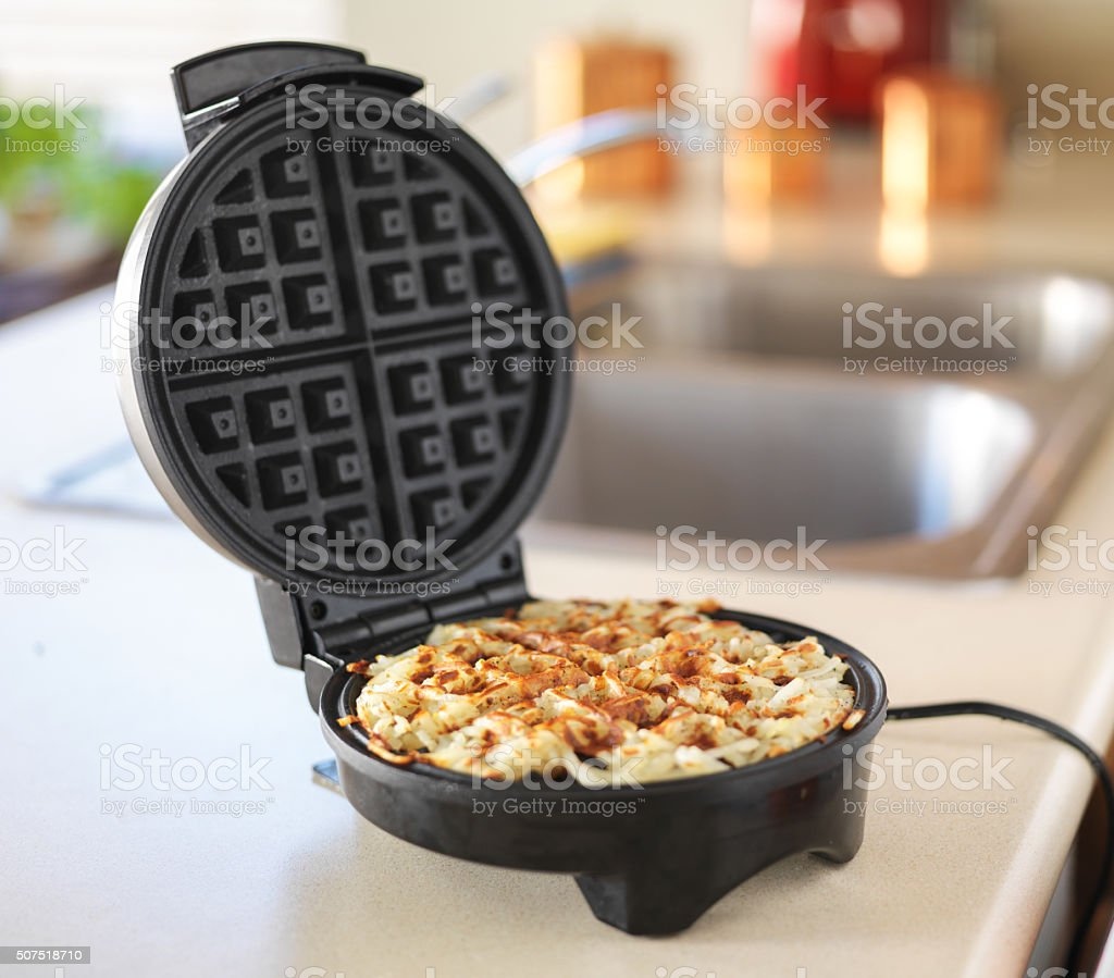 hash browns made in waffle maker kitchen hack stock photo