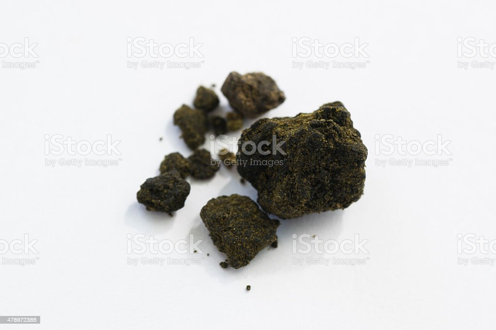 hashish pieces on white background macro stock photo