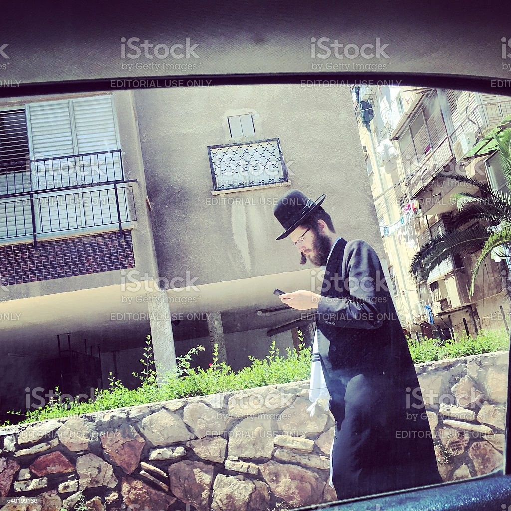 Hasidic man with mobile phone on Bnei Brak street, Israel stock photo