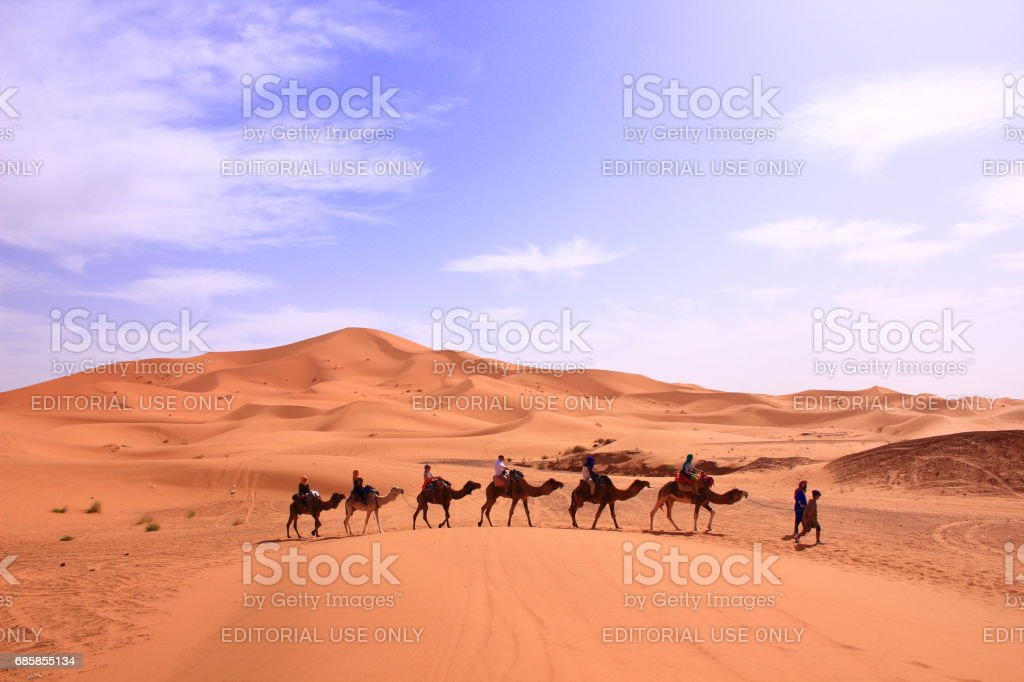 Hassilabied, Morocco - MAR 02th, 2017: People are taking camel in the sahara desert stock photo