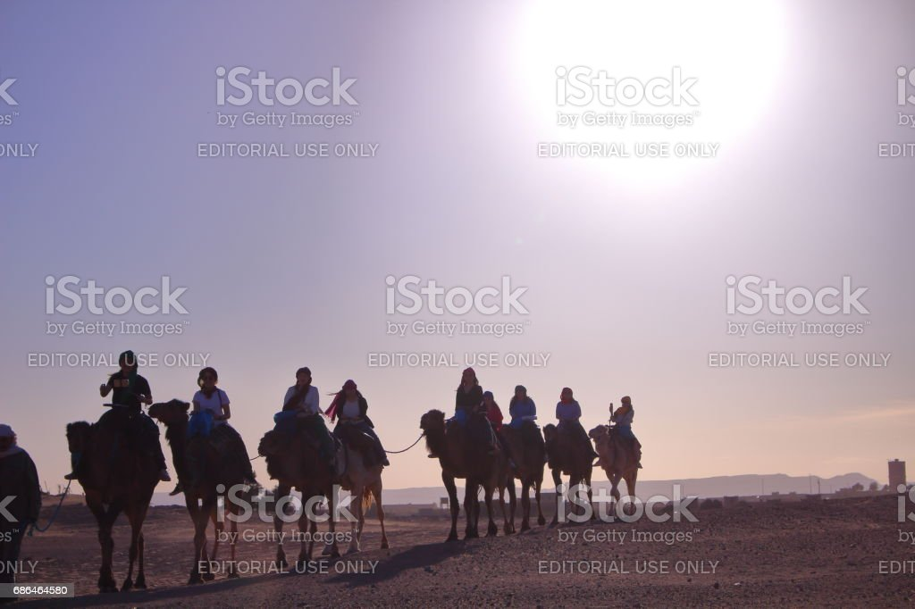 Hassilabied, Morocco - MAR 05th, 2017: People are taking camel in the sahara desert stock photo