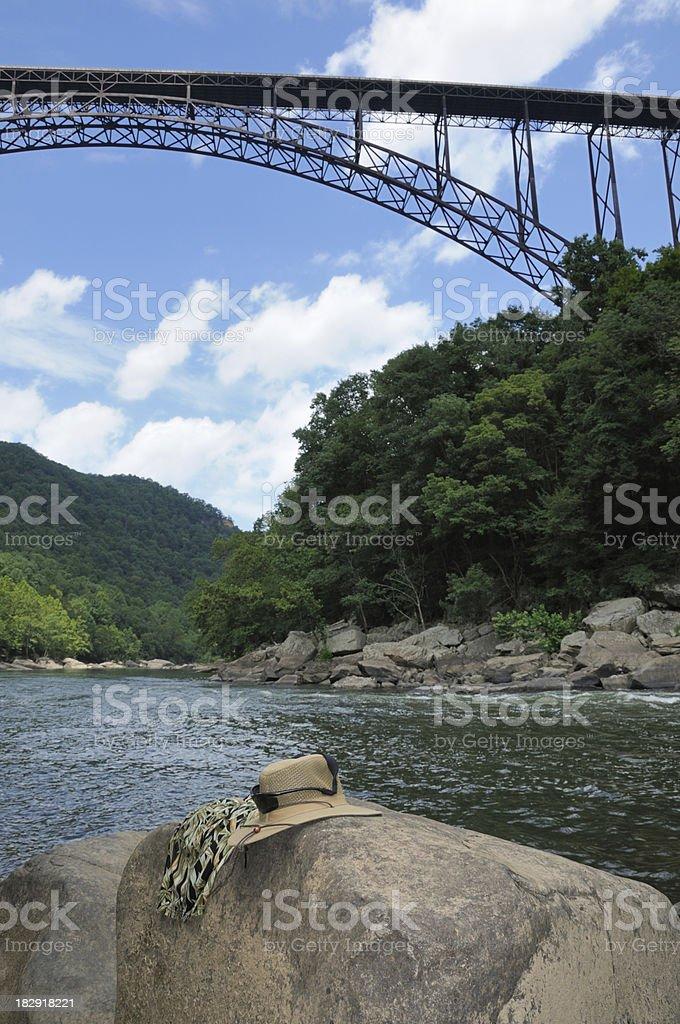 Hat and bathing suit on rock below bridge stock photo